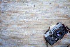 在木桌背景的老减速火箭的照相机 免版税库存图片