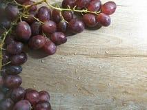 在木桌背景的葡萄 图库摄影