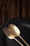 在木桌背景的黑空的板材叉子匙子 免版税库存照片