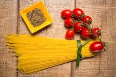 在木桌背景隔绝的意粉和罗马蕃茄 未煮过的意大利语干意粉 顶视图 库存照片