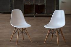 在木桌附近的两空的白色木脚凳在与木地板的顶楼内部 库存图片