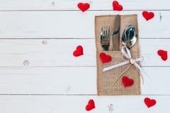 在木桌集合银器和红色心脏上为情人节 图库摄影
