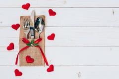 在木桌集合银器和红色心脏上为情人节 免版税库存照片