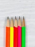 在木桌面上的五颜六色的铅笔技巧 免版税库存照片