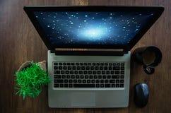 在木桌面上的便携式计算机 库存照片