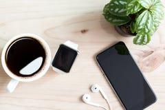 在木桌面上的电话和手手表 库存图片