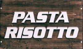 在木桌面团和意大利煨饭的标志 免版税库存图片