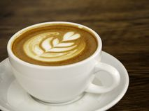 在木桌,咖啡时间上的加奶咖啡杯子 免版税库存照片