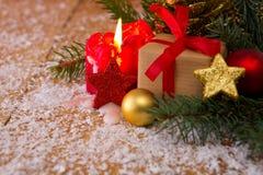 在木桌,圣诞树,红色蜡烛上的圣诞节礼物 免版税库存图片