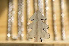 在木桌,在背景的反射,圣诞节链子上的木圣诞树 免版税图库摄影
