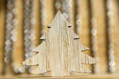 在木桌,在背景的反射,圣诞节链子上的木圣诞树 图库摄影