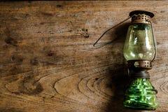 在木桌,葡萄酒颜色样式,老生锈的煤油的油灯 免版税库存图片