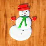 在木桌3d上的甜雪人糖果圣诞节礼物回报 库存图片
