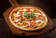 在木桨的新鲜的被烘烤的Margherita薄饼 免版税库存图片