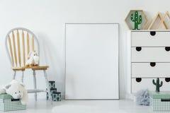 在木椅子安置的蓬松玩具在白色婴孩室内部wi 库存照片