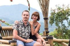 在木椅子的一对浪漫蜜月夫妇在热带巴厘岛,印度尼西亚山  库存图片