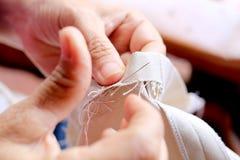 在木椅子的工作与她的布料、手工制造软的玩具缝合与毛毡的裁缝的手和针 免版税库存图片