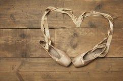 在木楼层上的二只芭蕾舞鞋 免版税库存图片