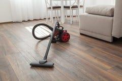 在木楼层上的吸尘器 清洁家 免版税库存图片