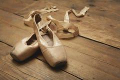 在木楼层上的芭蕾舞鞋 免版税图库摄影