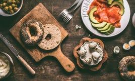 在木毁坏的委员会的切成两半的百吉卷小圆面包有面包刀和三明治成份的:三文鱼,鲕梨、hummus和鹌鹑蛋 免版税库存照片