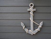 在木灰色背景的古色古香的船锚 免版税库存图片