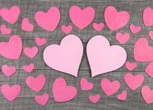 在木灰色破旧的别致的背景的桃红色心脏 免版税库存照片