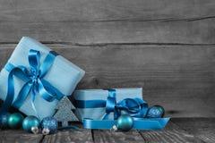 在木灰色破旧的背景的蓝色圣诞节礼物 图库摄影