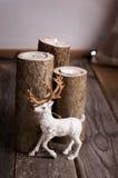 在木烛台的鹿近的灼烧的蜡烛 库存照片