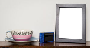 在木牍的空白的照片框架有茶杯的 免版税库存照片
