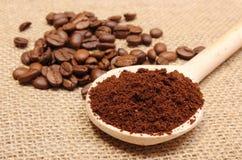 在木瓢的碾碎的咖啡和五谷在背景中 图库摄影