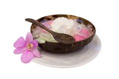 在木用桃红色兰花装饰的碗和木匙子的泰国点心 免版税库存图片