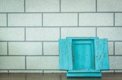 在木甲板和砖墙背景的蓝色照片框架 图库摄影