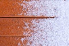 在木甲板板条的解冻新鲜的雪 库存图片
