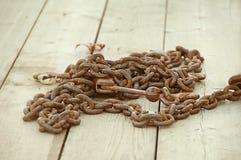 在木甲板的生锈的链子 免版税图库摄影