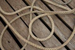在木甲板的结辨的绳索 免版税库存照片
