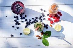在木白色背景的蓝莓, spinachy和橙色圆滑的人本质上 杯圆滑的人用莓果和薄菏 莓果, le 图库摄影