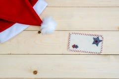 在木的减速火箭的被定调子的圣诞老人帽子 免版税库存图片