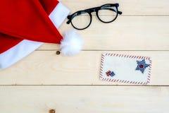 在木的减速火箭的被定调子的圣诞老人帽子 免版税库存照片