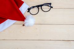 在木的减速火箭的被定调子的圣诞老人帽子 图库摄影