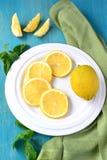 在木的白色盘切的新鲜的柠檬 免版税库存照片