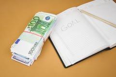 在木的白色笔记本一百欧元现金关闭背景  免版税库存图片