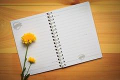 在木的空白的笔记本与黄色花 图库摄影