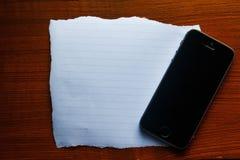 在木的纸与手机 免版税库存图片