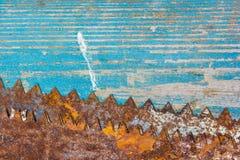 在木的蓝色的老生锈的锯被绘 免版税库存图片