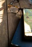 在木的镜片和葡萄酒旧书 免版税图库摄影