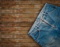 在木的难看的东西的牛仔布牛仔裤 免版税库存图片