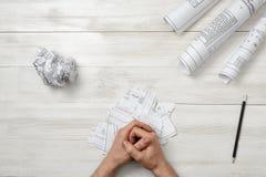 在木盘区的特写镜头男性被折叠的手与手折叠一张纸 免版税库存图片