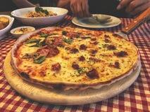 在木盘子供食的意大利薄饼 热的薄饼切片用熔化的乳酪 库存照片