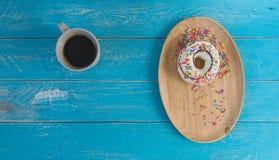 在木盘子和无奶咖啡的多福饼 库存图片